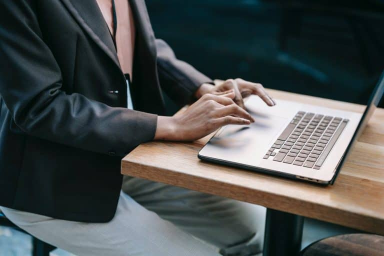 Person in Black Suit Jacket Using Macbook Pro