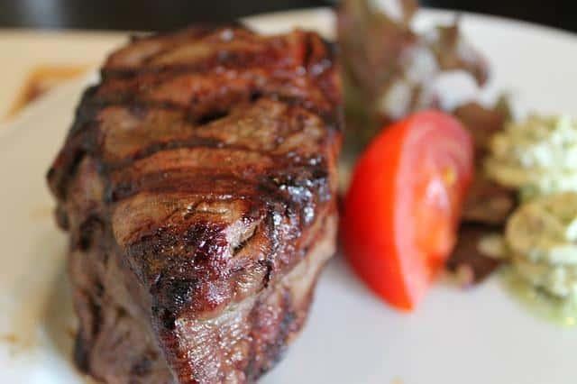 A closeup of steak with garnish